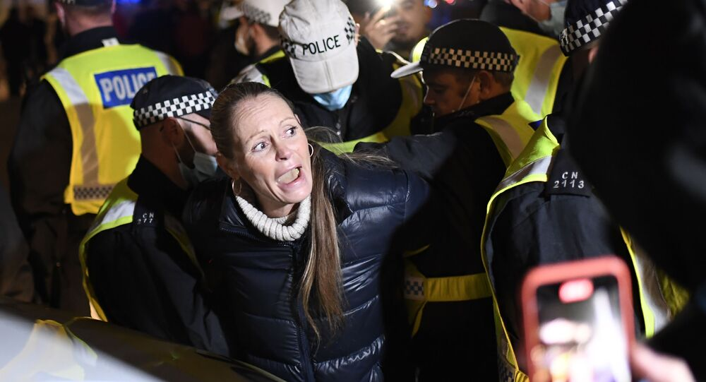 A woman is detained by police from 'The Million Mask March', an annual event described as a march against austerity, the infringement of rights, war crimes, corrupt politicians and to reinstate liberty, gather in Trafalgar Square in central London