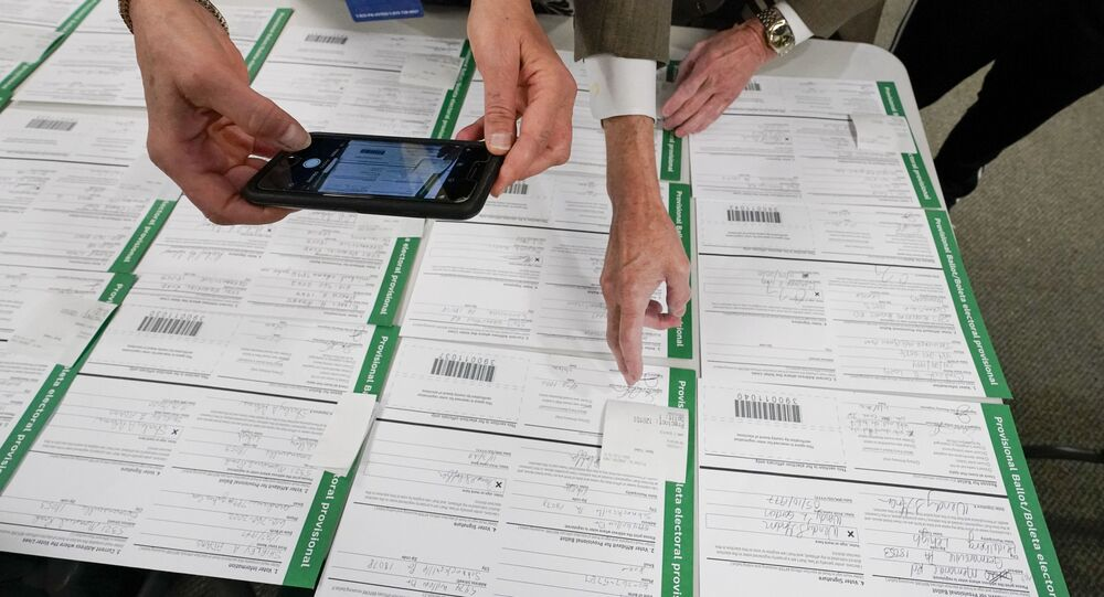 A canvas observer photographs Lehigh County provisional ballots as vote counting in the general election continues, Friday, Nov. 6, 2020, in Allentown, Pa