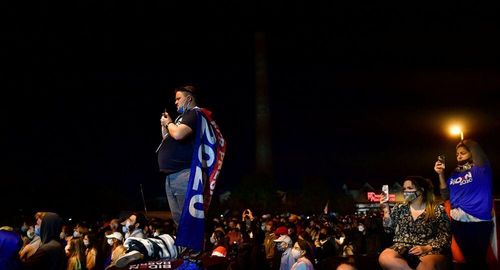 Supporters listen to U.S. President-elect Joe Biden's victory speech, in Wilmington, Delaware, U.S. November 7, 2020. REUTERS/Mark Makela