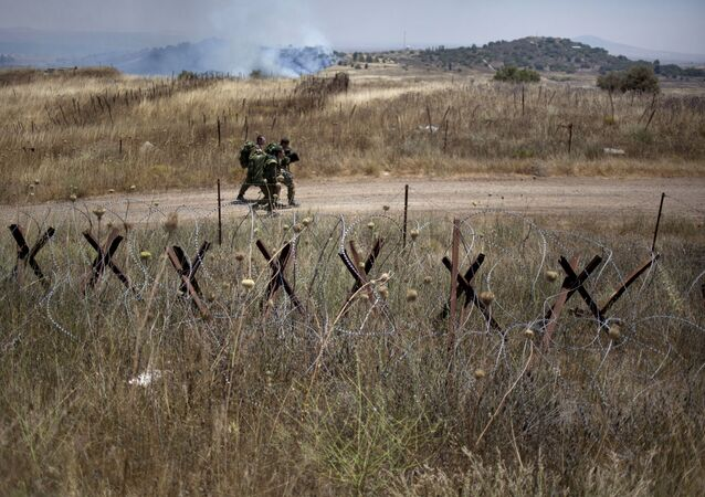 Israeli soldiers walk back from a position on the border with Syria on the Israeli controlled Golan Heights as smoke rises following explosions, Tuesday, July 16, 2013.