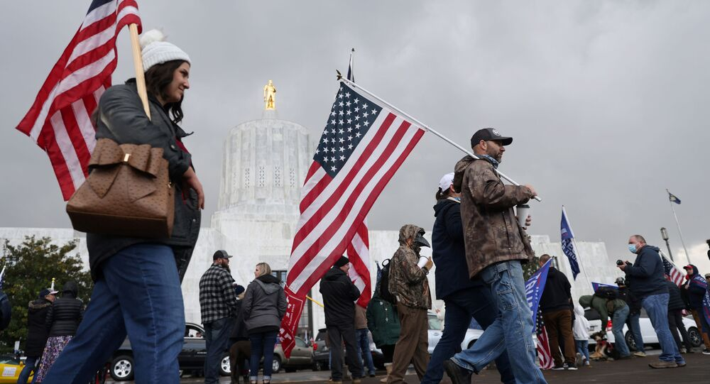 Supporters of U.S President Donald Trump carry U.S. flags during a protest after media announced that Democratic presidential nominee Joe Biden has won the election, in Salem, Oregon
