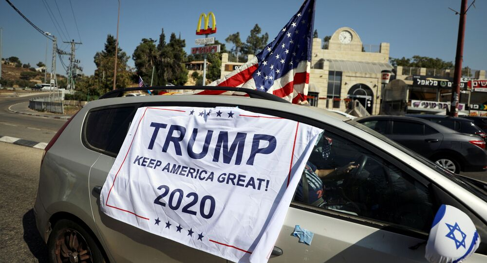 An American flag and banner cover a car, part of a convoy to the U.S. Embassy in Jerusalem to show support for U.S. President Donald Trump, ahead of the upcoming U.S. election, near Sho'eva, Israel October 27, 2020. REUTERS/Ammar Awad/File Photo