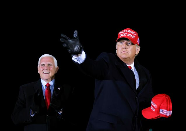 U.S. President Donald Trump hands out caps to supporters next to Vice President Mike Pence, as he holds a campaign rally at Gerald R. Ford International Airport in Grand Rapids, Michigan, U.S., November 2, 2020. REUTERS/Carlos Barria