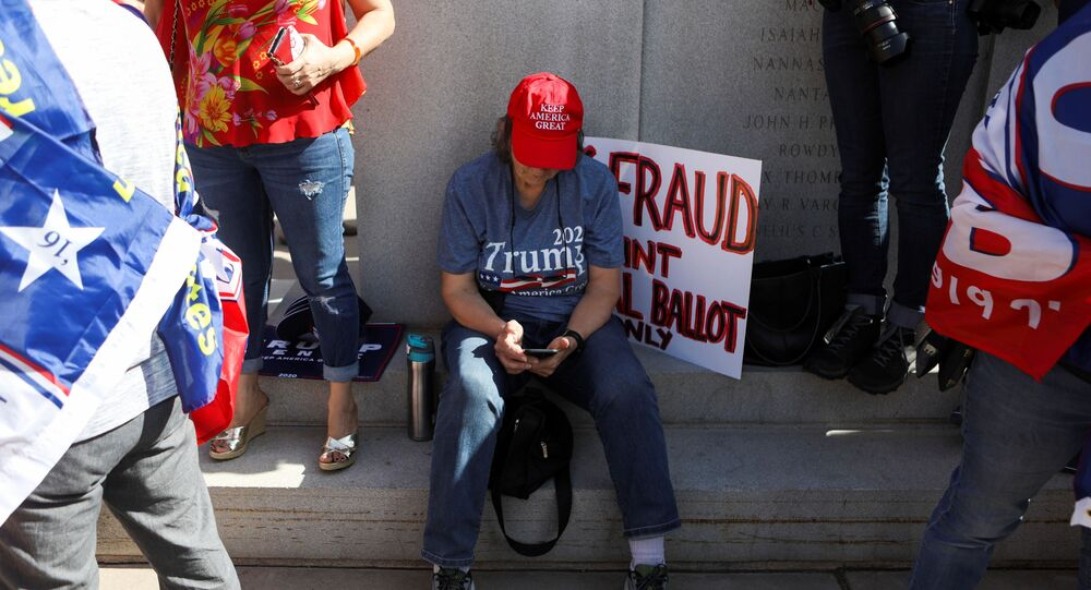"A supporter of U.S. President Donald Trump looks at her phone as others gather at a ""Stop the Steal"" protest after the 2020 U.S. presidential election was called for Democratic candidate Joe Biden, in front of the Arizona State Capitol in Phoenix, Arizona, U.S., November 7, 2020."