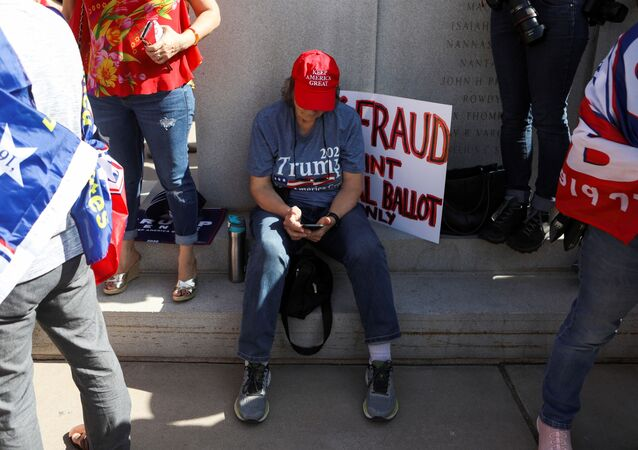 """A supporter of U.S. President Donald Trump looks at her phone as others gather at a """"Stop the Steal"""" protest after the 2020 U.S. presidential election was called for Democratic candidate Joe Biden, in front of the Arizona State Capitol in Phoenix, Arizona, U.S., November 7, 2020."""