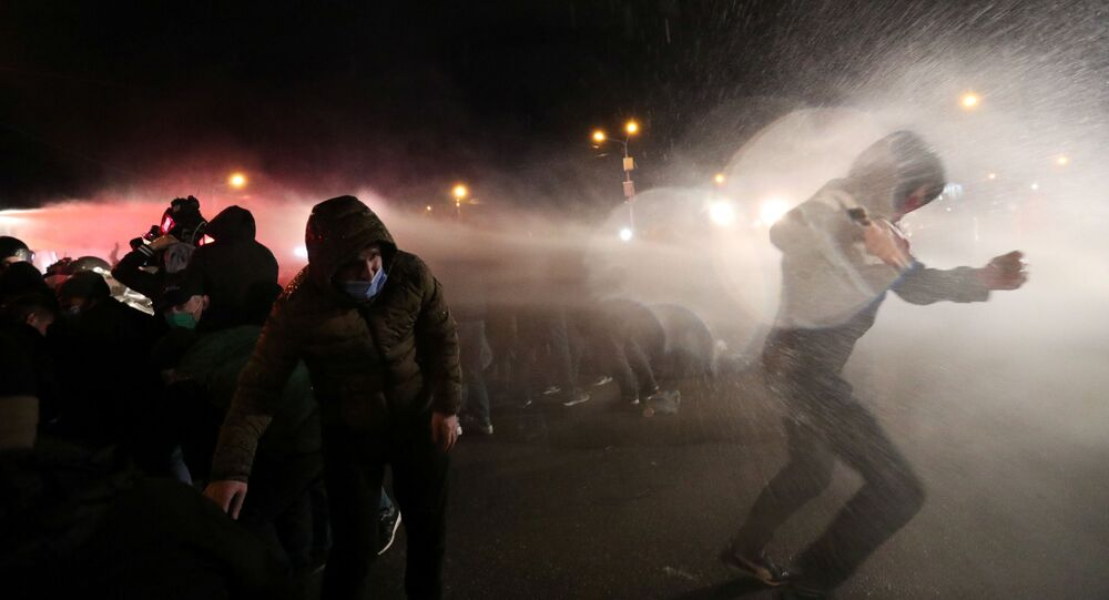 Demonstrators react as riot police use a water cannon during an opposition rally against the results of a parliamentary election, outside the Central Election Commission (CEC) building in Tbilisi, Georgia November 9, 2020.