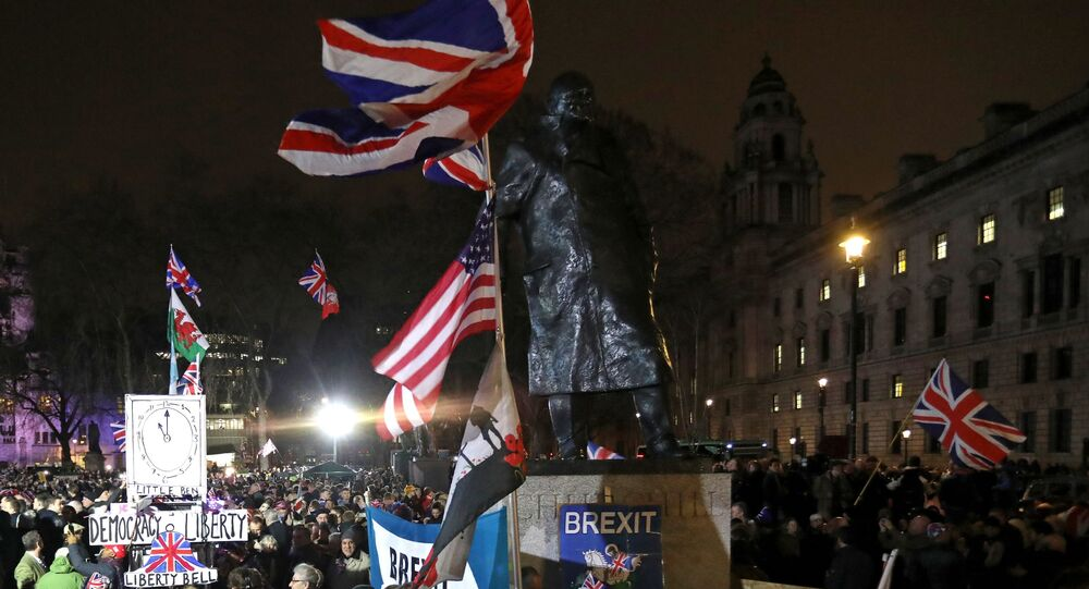 Brexit supporter wave Union flags as they wait near a statue of British war-time Prime Minister Winston Churchill, for the festivities to begin in Parliament Square, the venue for the Leave Means Leave Brexit Celebration in central London on January 31, 2020, the day that the UK formally leaves the European Union