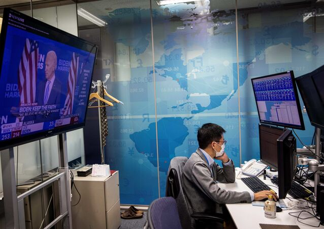 A currency trader works at his desk as a screen (L) shows news updates on the US presidential election featuring an image of Democratic Party candidate Joe Biden, at a foreign exchange trading company in Tokyo on November 5, 2020