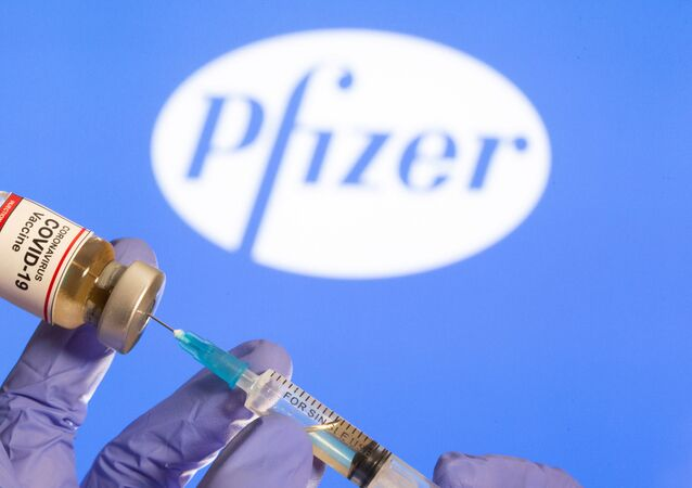 A woman holds a small bottle labeled with a Coronavirus COVID-19 Vaccine sticker and a medical syringe in front of displayed Pfizer logo in this illustration taken, October 30, 2020.