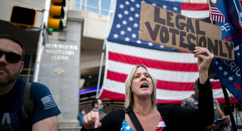 Carri Dusza, a supporter of President Donald Trump, holds a placard stating LEGAL VOTES ONLY while shouting across the street at supporters of President-elect Joe Biden the day after a presidential election victory was called for Biden, in Philadelphia, Pennsylvania, U.S. November 8, 2020.