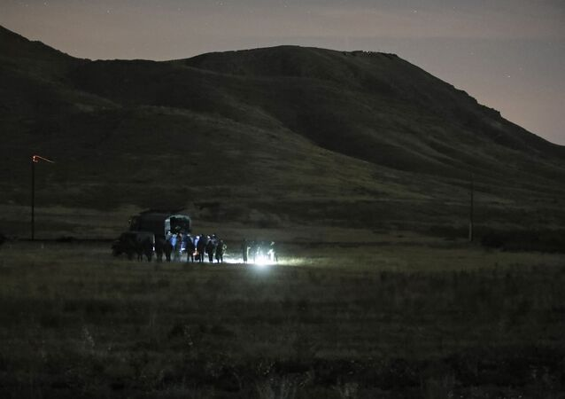 Armenian and Russian soldiers search the site of wreckage of a downed Russian military helicopter which was shot down in Armenia near the border with Azerbaijan, near Eraskh, Armenia, Monday, Nov. 9, 2020.