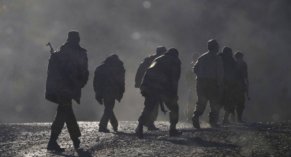 Ethnic Armenian soldiers walk along the road near the border between Nagorno-Karabakh and Armenia, Sunday, Nov. 8, 2020.
