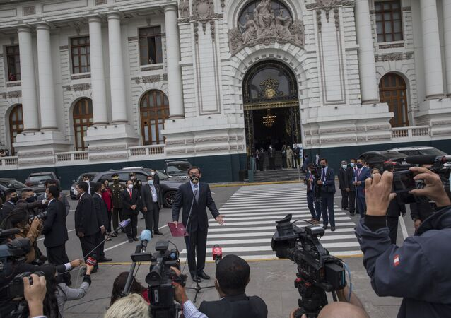 Peruvian President Martin Vizcarra talks to reporters before entering Congress where he faces an impeachment vote in Lima, Peru, Monday, Nov. 9, 2020.