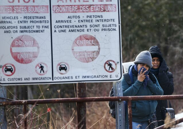 Two people, who later indicated to officials they are from Sudan, hesitate as they listen to a Royal Canadian Mounted Police officer tell them they will be taken into custody just before they crossed into Canada from Perry Mills, N.Y., near Hemmingford, Quebec, Sunday, Feb. 26, 2017