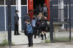Year seven pupils are directed to socially distance as they arrive for their first day at Kingsdale Foundation School in London, Thursday, Sept. 3, 2020