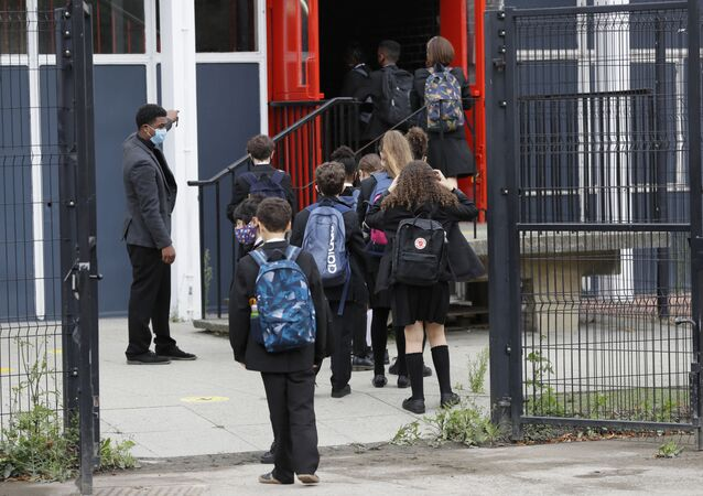 Year seven pupils are directed to socially distance as they arrive for their first day at Kingsdale Foundation School in London, Thursday, 3 September 2020