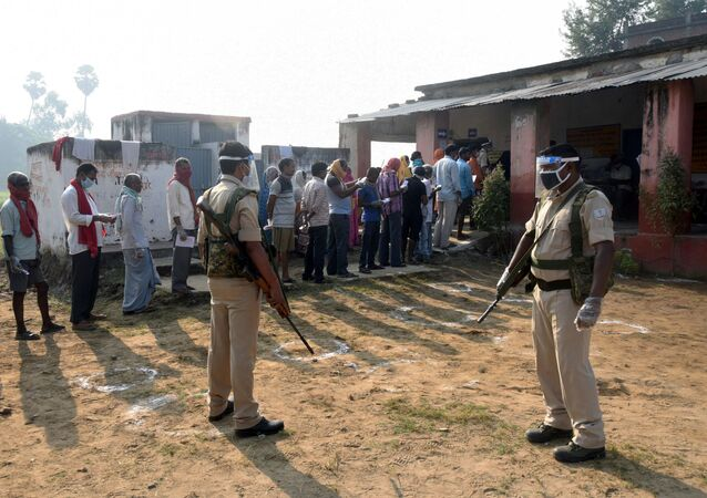 Policemen wearing protective face shields stand guard as voters stand in a queue to cast their vote outside a polling booth during the state assembly election, amidst the spread of the coronavirus disease (COVID-19), at a village on the outskirts of Patna, in the eastern state of Bihar, India, October 28, 2020