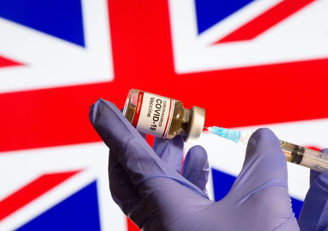 A woman holds a small bottle labeled with a Coronavirus COVID-19 Vaccine sticker and a medical syringe in front of displayed UK flag in this illustration taken, October 30, 2020