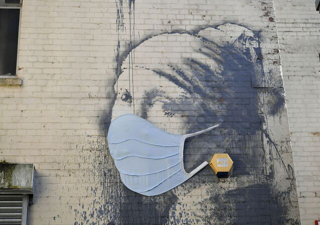 Banksy's Girl with a Pierced Eardrum mural has been given a face mask in a nod to the coronavirus pandemic as the UK continues in lockdown to help curb the spread of the coronavirus, in Bristol, England, Wednesday April 22, 2020