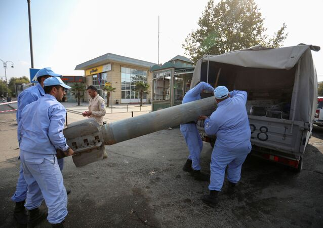 Azeri investigators load a fragment of an artillery shell in a street recently hit by shelling during a military conflict over the breakaway region of Nagorno-Karabakh, in the town of Barda, Azerbaijan October 29, 2020