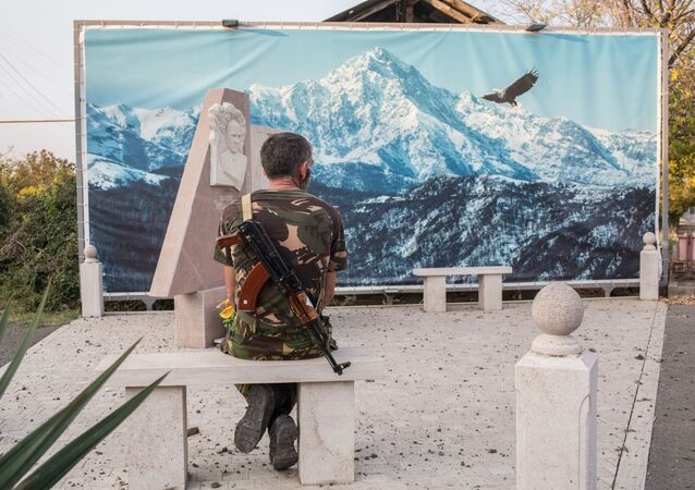 An Armenian soldier looks at the picture sitting on a stone bench in Martakert, the self-proclaimed Nagorno-Karabakh Republic