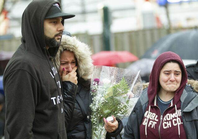 Mourners grieve after placing a memorial at a vigil in April 2018 in Toronto, Canada after Alek Minassian drove his van into a crowd.
