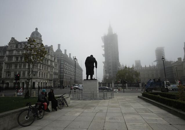 People sit talking near the statue of Winston Churchill and the scaffolded Houses of Parliament and the Elizabeth Tower, known as Big Ben, shrouded in fog, on the first day of Britain's second lockdown designed to save its health care system from being overwhelmed by people with coronavirus, in London, Thursday, Nov. 5, 2020