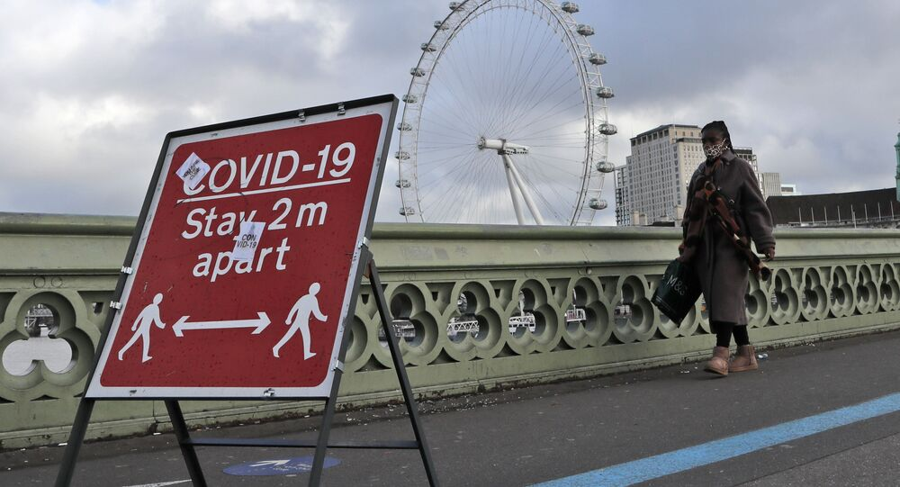 A woman walks over Westminster Bridge during the second coronavirus lockdown in London, Tuesday, Nov. 10, 2020. Britain's lockdown will run until at least Dec. 2., shuttering restaurants, hairdressers and clothing stores.