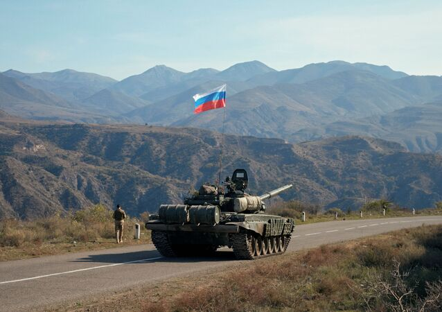 A service member of the Russian peacekeeping troops walks near a tank near the border with Armenia, following the signing of a deal to end the military conflict between Azerbaijan and ethnic Armenian forces, in the region of Nagorno-Karabakh, November 10, 2020.