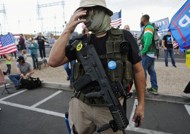 A Trump supporter carries a semi-automatic rifle at a Stop the Steal protest after the 2020 U.S. presidential election was called for Democratic candidate Joe Biden, in front of the Maricopa County Tabulation and Election Center (MCTEC), in Phoenix, Arizona, U.S., November 7, 2020