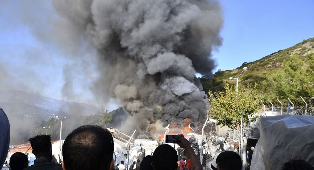 Migrants watch smoke rising from a fire inside a refugee camp on the eastern Aegean island of Samos, Greece, Wednesday, Nov. 11, 2020. Dozens of accommodations were destroyed by the fire that broke out on Wednesday morning, two weeks after an earthquake hit the island.