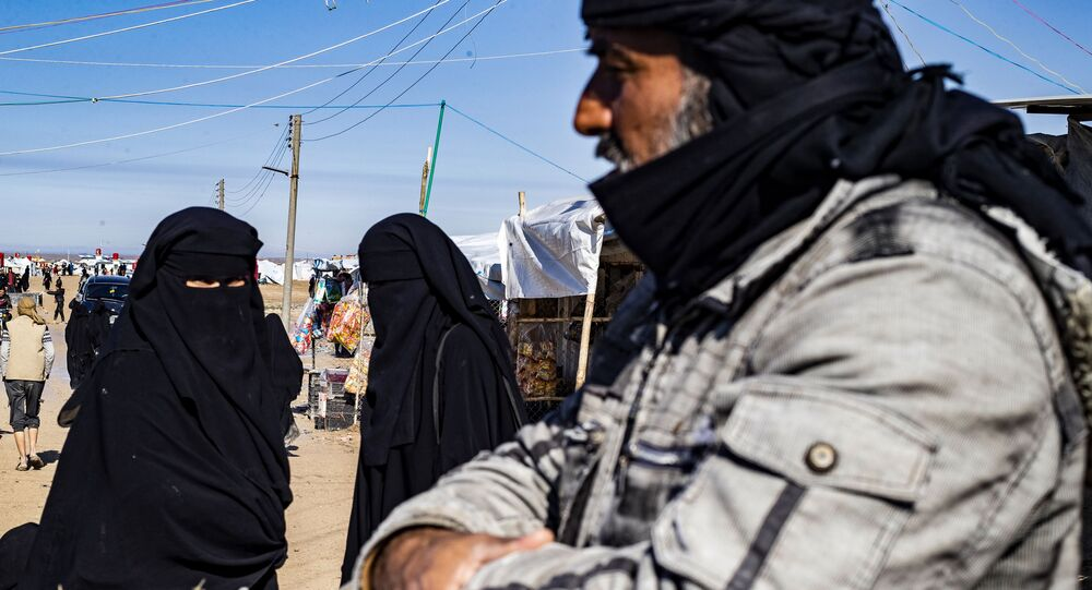 Two women chat as a man looks on at the Kurdish-run al-Hol camp in the al-Hasakeh governorate in northeastern Syria on January 25, 2020, where families of Islamic State (IS) foreign fighters are held
