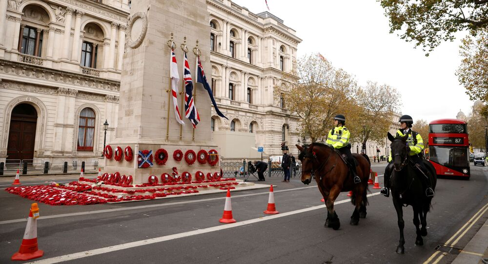 Mounted police officers pass the Cenotaph with wreaths on it in Whitehall, London, England, 11 November 2020.