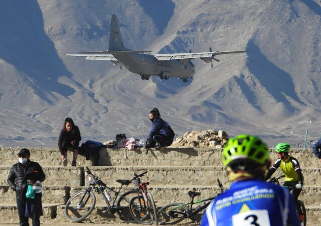 An Indian Air Force aircraft flies past cyclists near a mountain range in Leh, the joint capital of the union territory of Ladakh bordering China, on October 27, 2020
