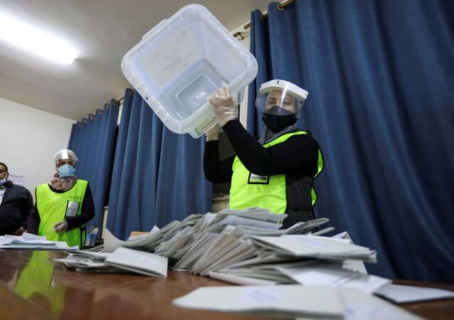 An election official wearing a protective mask empties a ballot box after parliamentary elections, amid fears over the rising number of the coronavirus (COVID-19) infections, in Amman, Jordan 10 November 2020.
