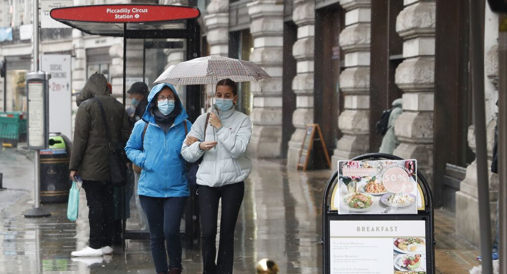 People wearing masks to help prevent the spread of the coronavirus walk along Regent Street in London, Thursday, Oct. 29, 2020. Around 100,000 people are catching the coronavirus every day in England, according to the latest Imperial College London study.
