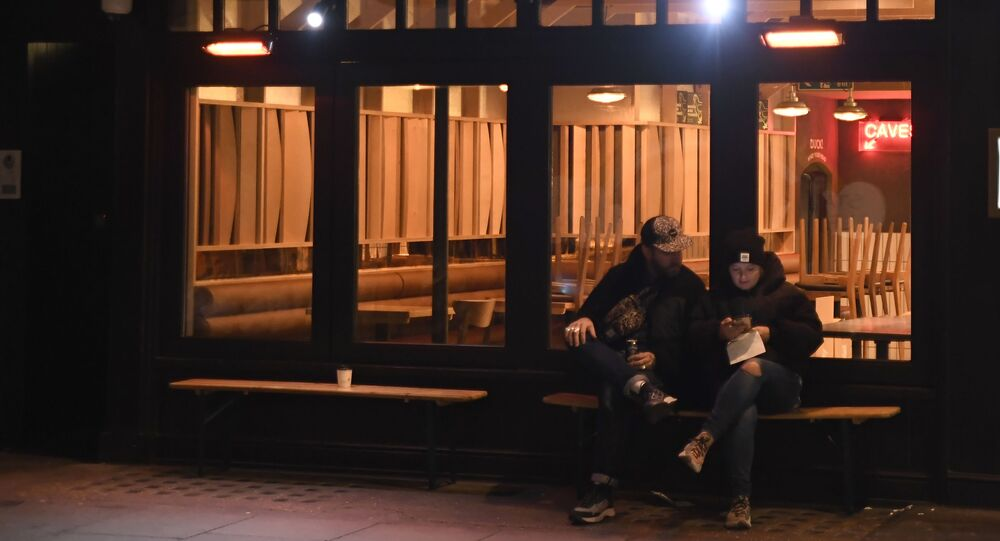 Two people sit outside a closed bar as restaurants and shops in the Soho area are now shut due to a second lockdown in central London, Thursday, Nov. 5, 202