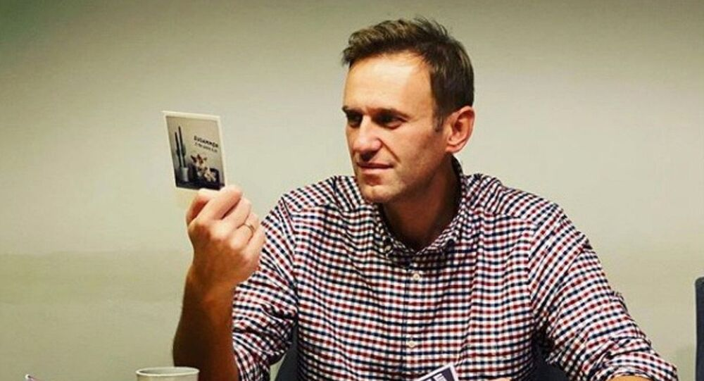 Russian opposition politician Alexei Navalny reads cards and letters from his supporters in an unknown location, in this undated image obtained from social media October 18, 2020