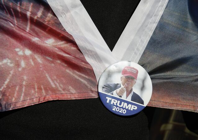 A woman wears a Trump button as supporters of President Donald Trump protest outside the Pennsylvania Convention Center, where vote counting continues, in Philadelphia, Monday, Nov. 9, 2020
