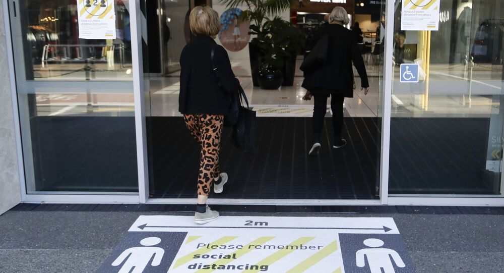Shoppers walk into a shopping mall past social distancing signs in Christchurch, New Zealand, 8 June 2000