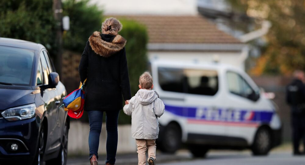 A woman holds her child by the hand on their way to the school in the area around the Bois d'Aulne college where Samuel Paty, the French teacher, was beheaded on the streets of the Paris suburb of Conflans-Sainte-Honorine, France, November 2, 2020