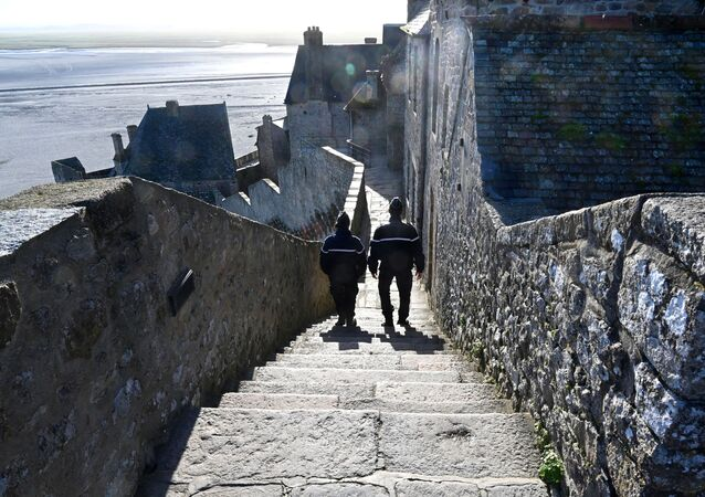 French gendarmes patrol on the defensive wall walk in Le Mont-Saint-Michel, Normandy, northwestern France, on November 12, 2020, as France is on a second lockdown aimed at containing the spread of Covid-19 pandemic caused by the novel coronavirus.