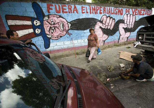 A man speaks to a pedestrian next to a graffiti that reads Imperialism get out of Venezuela at Catia shanty town, in Caracas, Thursday, Nov. 15, 2007
