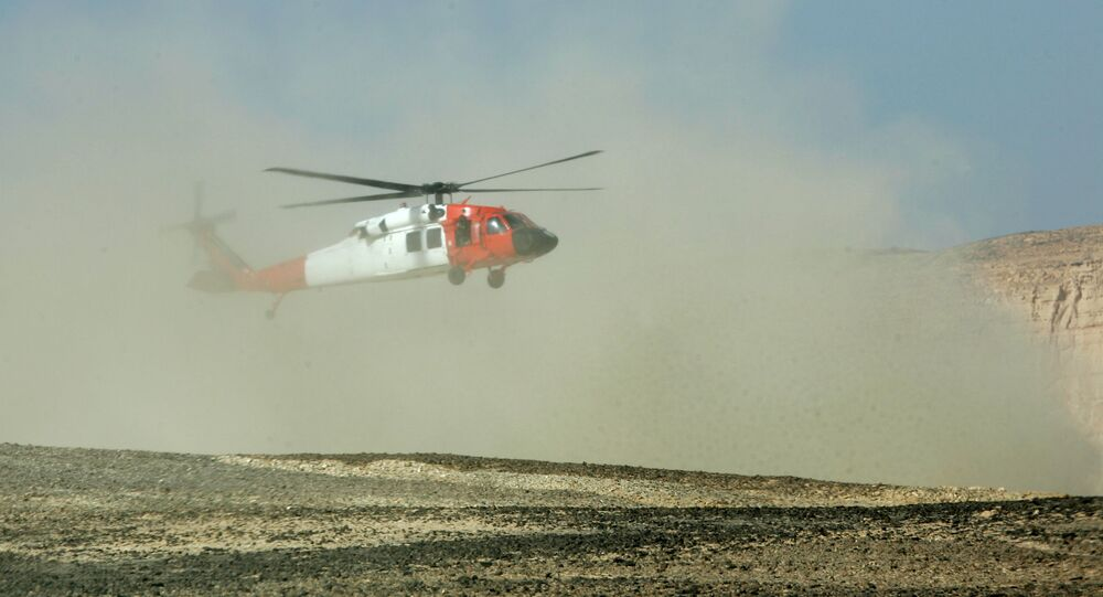 A helicopter creates a cloud of dust as it lands near the scene of the plane crash which killed nine foreign peacekeepers near the village of El-Thamad in the Sinai region of Egypt Sunday, May 6, 2007