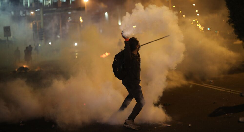 A protester returns a tear gas canister launched by police to disperse protesters who are trying to march to Congress in a demonstration against the removal of President Martin Vizcarra, in Lima, Peru, Thursday, Nov. 12, 2020.