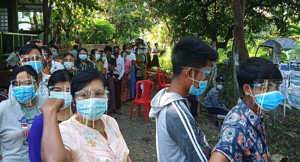 People wearing protective gear line up to vote at a polling station during the general election in Taungup, Rakhine State, Myanmar, November 8, 2020. Picture taken November 8, 2020