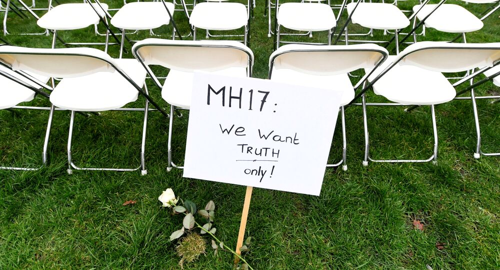 FILE PHOTO: A protest sign stands in front of a row of chairs as family members of victims of the MH17 crash lined up empty chairs for each seat on the plane during a protest outside the Russian Embassy in The Hague, Netherlands 8 March 2020.