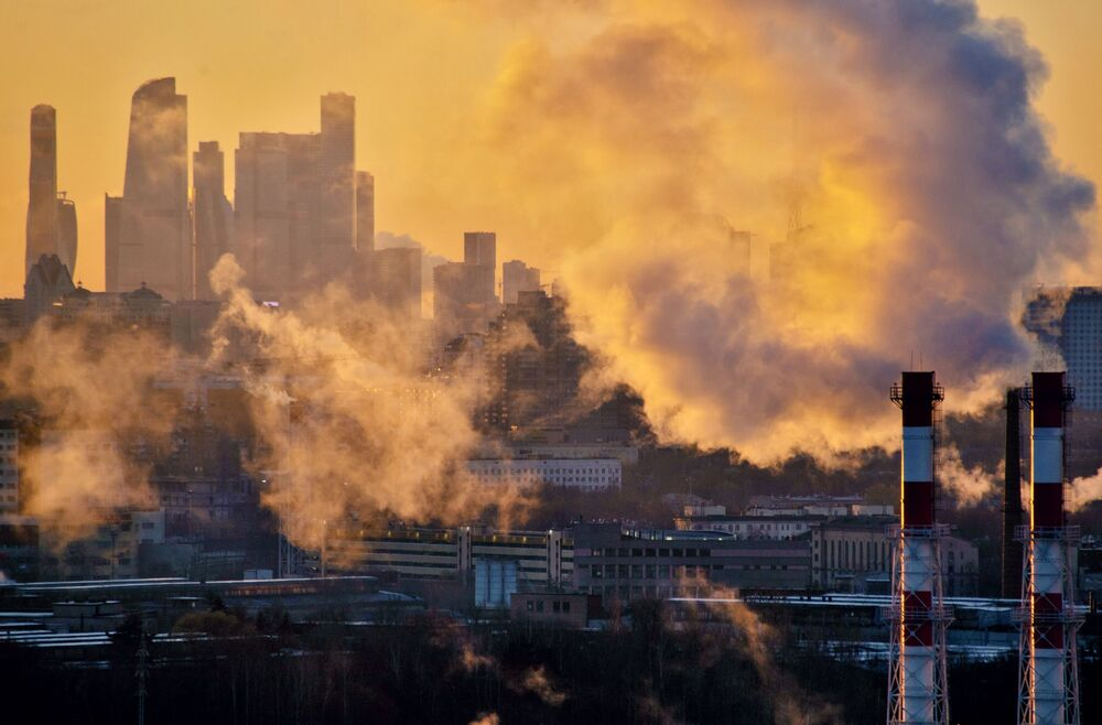 Smoke from power-plant pipes rises into the sky as the Moscow City district is seen in the background.