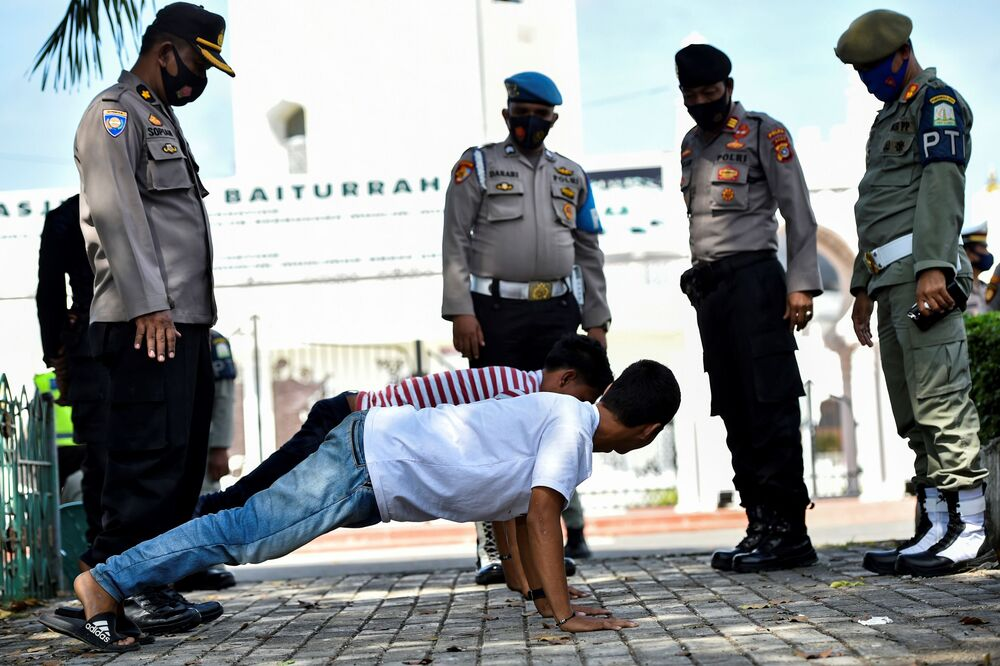 Members of the public perform press-ups as punishment for not wearing face masks amid the Covid-19 coronavirus pandemic in Banda Aceh, Indonesia on 10 November 2020.