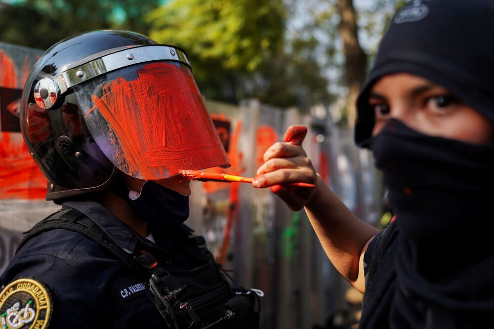 A member of a feminist collective paints the helmet of a riot police officer during a protest against gender and police violence, in Mexico City, Mexico 11 November 2020.
